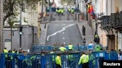 Policías ecuatorianos custodian un retén a poca distancia del Palacio Presidencial en Quito. El Presidente trasladó sus operaciones a la porteña ciudad de Guayaquil.
