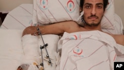 Syrian Ejnad Akkad, a fighter for the Syrian opposition Free Syrian Army, who was wounded by a mine planted by the Islamic State group near the border with Turkey, lays on his bed at a hospital in Kilis, Turkey, Feb. 9, 2016.