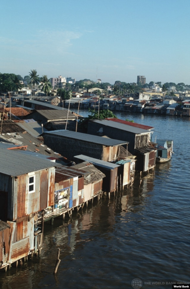 Shanty-town on the Saigon River; with downtown Saigon in the background. Urban planning aims to minimize slums caused by rural migration.(World Bank)