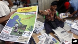 A man at a market in Rangoon, shows a People's Age private journal featuring an article written by Burma's pro-democracy leader Aung San Suu Kyi, September 6, 2011.