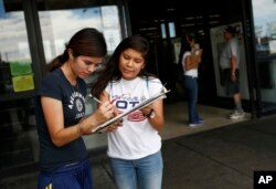 Fabiola Vejar, right, registers Stephanie Cardenas to vote in front of a Latino supermarket in Las Vegas in June 2016. (AP)