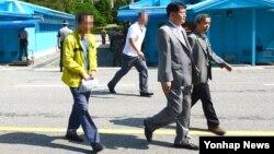제3국을 통해 북한에 들어갔던 김모(52·황색 옷) 씨가 11일 판문점을 통해 한국으로 귀환하고 있다.