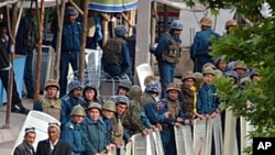 Uzbeks walk along line of riot police as they secure the area near checkpoint in the town of Korasuv at the Kyrgyz-Uzbek border (file photo).