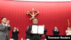 북한 김정은 국무위원장이 17일 평양에서 열린 노동당 중앙위원회 제8기 제3차 전원회의 3일차 회의에서 자신이 서명한 문서를 들어보이고 있다.