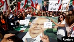 Supporters of Lebanon's President Michel Aoun hold his poster during a rally in Baabda near Beirut, Lebanon, November 3, 2019. REUTERS/Goran Tomasevic