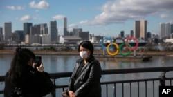 1月29日,一名戴上口罩的遊客在東京以奧運會的標誌為北京拍照。
