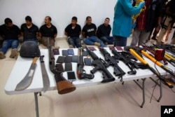 FILE - Suspects in the assassination of Haiti's President Jovenel Moise are shown to the media, along with the weapons and equipment they allegedly used in the attack, in Port-au-Prince, Haiti, July 8, 2021.