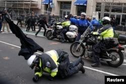 Un policía cae al suelo mientras otro lanza gas pimienta a manifestantes anti-Trump en el centro de Washington.