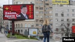 រូបឯកសារ៖ ស្ត្រីម្នាក់ដើរកាត់ផ្ទាំងប៉ាណូមួយដែលសរសេរថា «សូមថ្លែងអំណរគុណ បង Xi» ក្នុងទីក្រុងប៊ែលក្រាដ ប្រទេសស៊ែកប៊ី កាលពីថ្ងៃទី១ ខែមេសា ឆ្នាំ២០២១។