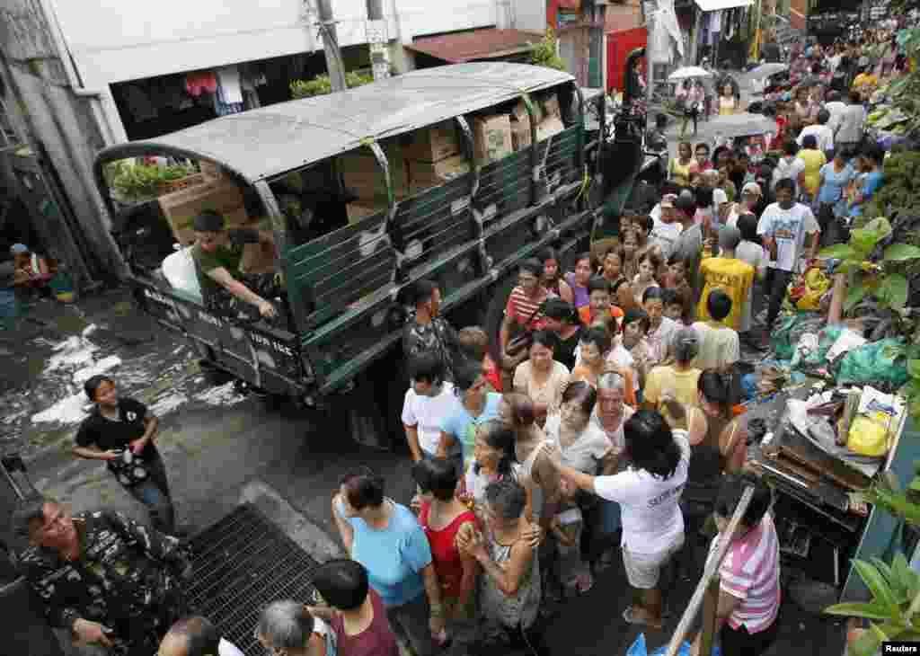 Người dân xếp hàng nhận đồ cứu trợ sau khi những căn nhà tạm bợ của họ bị nhấn chìm trong nước lũ do mưa mùa ở Sta Mesa, thủ đô Manila, 13 tháng 8, 2012.