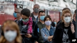 Passengers with face masks arrive in the main train station in Frankfurt, Germany, Aug. 27, 2020.