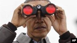 Tổng thống Obama dùng ống nhòm nhìn sang phía bên kia phần đất của Bắc Triều Tiên từ khu phi quân chia cắt hai miền Triều Tiên tại Panmunjom, Hàn Quốc, ngày 25/3/2012