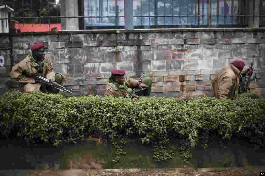 Des soldats kenyans s'abritent derrière un pan de mur près du Westgate Mall de Nairobi, le 23 septembre 2013.
