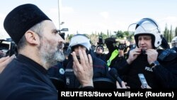 Montenegro, Podgorica, A Serbian Orthodox Church priest speaks with a riot policeman on a bridge near the parliament