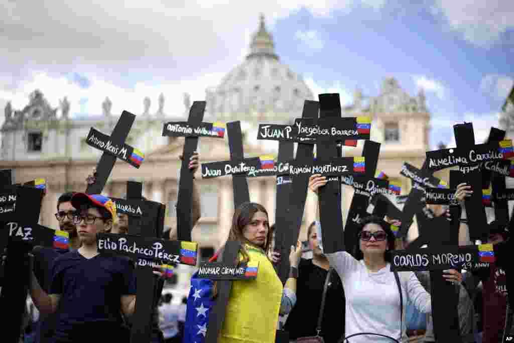 បាតុករកាន់ឈើឆ្កាងដែលមានទង់ជាតិរបស់ប្រទេសវ៉េណេស៊ុយអេឡា និងមានឈ្មោះរបស់អ្នកដែលត្រូវបានគេសម្លាប់នៅក្នុងបាតុកម្មហិង្សា ដែលអំពាវនាវឲ្យលោកប្រធានាធិបតី Nicolas Maduro ចុះចេញពីតំណែង ប្រមូលផ្តុំនៅក្នុងទីលាន St. Peter's Square នៅបុរីវ៉ាទីកង់។