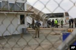 Amapholisa amukele abaxotshwe kwele Bhilithane ngoLwesine eRobert Mugabe International Airport. (AP)