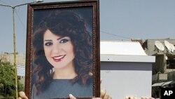 Người đi đám tang mang theo hình cô Dima Farah, người bị giết chết trong vụ đánh bom tự sát hôm 10 tháng 5, 2012 tại Damascus