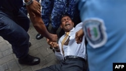 Maldives police try to move former president Mohamed Nasheed during a scuffle as he arrives at a courthouse in Male, Feb. 23, 2015.