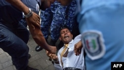 FILE - Maldives police try to move former president Mohamed Nasheed during a scuffle as he arrives at a courthouse in Male, February 23, 2015.