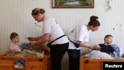 Professional nurse Laura Murphy (R) and volunteer Loretta Gaughan from Ireland feed children at an orphanage for mentally disabled children under the Vesnova institution, near the Belarussian village of Vesnova, June 6, 2013.