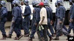 Zimbabwean police arrest an MDC supporter in Harare recently … Activists say ongoing political unrest in Zimbabwe makes it dangerous for migrants in South Africa to return to their homeland