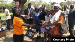 Parents of children at a Zimbabwean school receiving new shoes from Shoes for Healing Campaign.