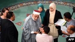Abdelfattah Mouro, center, deputy president of the Tunisian Assembly, speaks with deputies during debate on anti-terror legislation in Tunis, July 24, 2015.