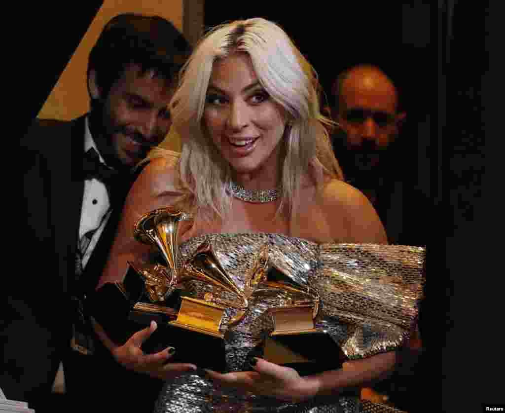"Lady Gaga poses backstage with her awards for Best Song Written for Visual Media and Best Pop Duo/Group Performance for ""Shallow"" and her Best Pop Solo Performance for ""Joanne (Where do You Think You're Goin?)"" during the 61st Grammy Awards in Los Angeles, California, Feb. 10, 2019."