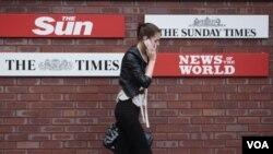 Seorang perempuan Inggris lewat di depan kantor pusat tabloid News of the World di London (7/7).