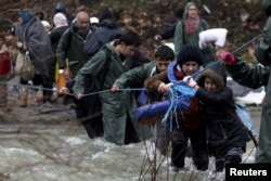 Refugees and migrants attempt to cross a river near the Greek-Macedonian border to enter Macedonia after an unsuccessful attempt yesterday, west of the village of Idomeni, Greece, March 15, 2016.
