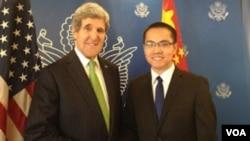 资料照:原任腾讯财经频道编导的张贾龙(右)会见前美国国务卿约翰·克里。(维权网图片)