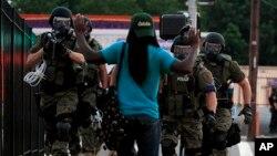 Cảnh sát trang phục chống bạo động tiến về phía một người đàn ông ở Ferguson, Missouri, ngày 11/8/2014.