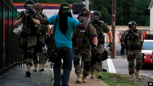 Police wearing riot gear walk toward a man with his hands raised,  in Ferguson, Missouri, Aug. 11, 2014.