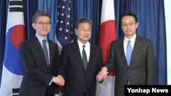 FILE - South Korea's Special Representative Kim Hong-kyun, U.S. State Department's Special Representative Joseph Yun and Japanese Director-General Kenji Kanasugi pose for a photo after their meeting at the US State Department on Feb. 27, 2017.
