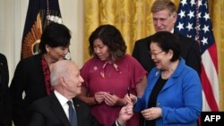 President Joe Biden hands a pen to Sen. Mazie Hirono, D-Hawaii, after signing the COVID-19 Hate Crimes Act, in the East Room of the White House in Washington, May 20, 2021.