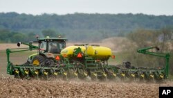 FILE - A farmer plants soybeans in a field in Springfield, Neb., May 23, 2019.