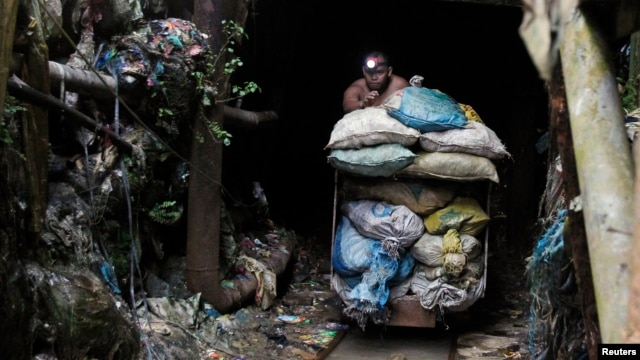 A Filipino miner pushes a cart containing sacks of mineral muck ore in the Compostela Valley, southern Philippines. May 24, 2012