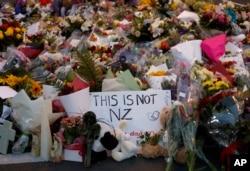 """Flores pelas vítimas do ataque de 15 de Março, com um cartaz que diz """"Isto não é a Nova Zelândia"""""""