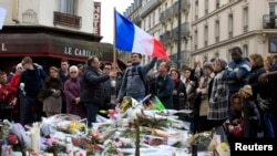 FILE - People pay tribute to victims outside Le Carillon restaurant, one of the attack sites in Paris, Nov. 16, 2015.
