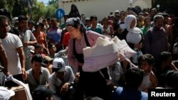 A migrant woman exits the police station carrying her infant baby as other migrants line up for a registration procedure on the Greek island of Kos, Aug. 18, 2015.
