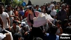 Seorang perempuan membawa bayinya di antara para migran lainnya di Pulau Kos, Yunani (18/8).