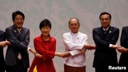 지난해 11월 미얀마 네피도에서 열린 아세안 정상회의에 참가한 한-중-일 정상들이 손을 맞잡고 있다. 왼쪽부터 아베 신조 일본 총리, 박근혜 한국 대통령, 테인 셰인 미얀마 대통령, 리커창 중국 총리. (자료사진)