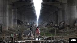 រូបភាពឯកសារ៖ មនុស្សម្នាដើរនៅលើស្ពានឈើមួយ កាត់លូទឹកស្អុយ នៅក្នុងក្រុង Danapur រដ្ឋ Bihar ប្រទេសឥណ្ឌា កាលពីថ្ងៃទី៧ ខែមេសា ឆ្នាំ២០១៩។