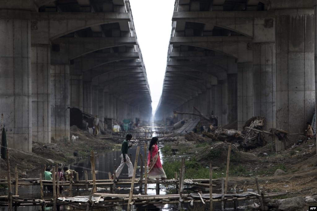 인도 비하르 주 다나푸르의 디가(Digha) 다리 아래에서 주민들이 수로를 건너기 위해 임시로 만들어 놓은 다리 위를 걷고 있다.