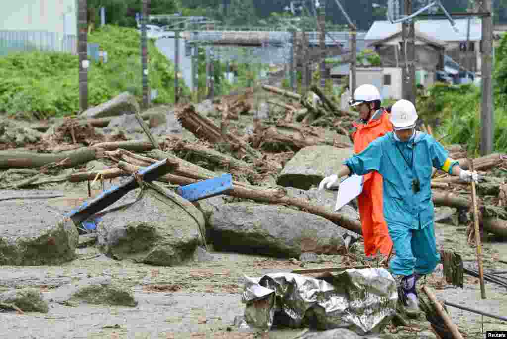 Workers walk among debris after a landslide caused by heavy rains due to Typhoon Neoguri in Nagiso town, Nagano prefecture, in this photo taken by Kyodo, July 10, 2014.