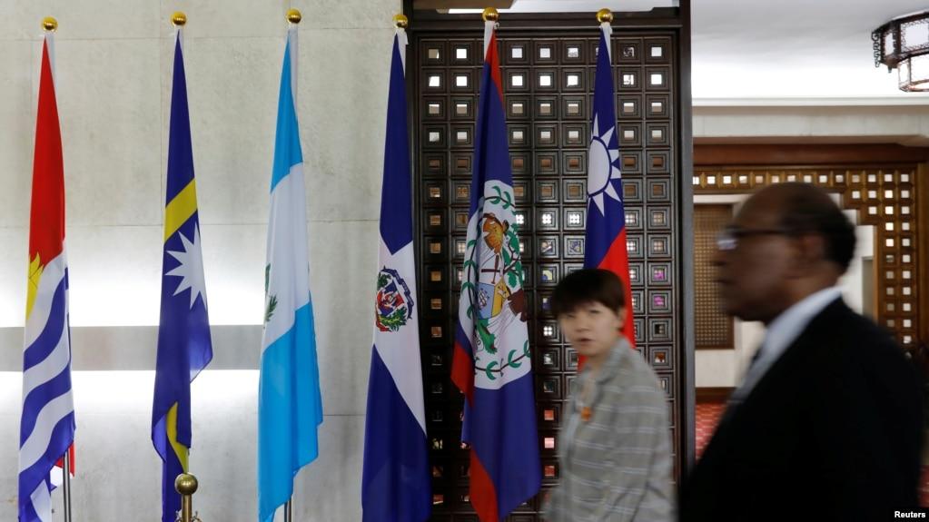 人们在台湾外交部内走过多米尼加国旗(右三)。(2018年5月1日)