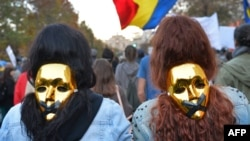 People wear golden masks during a protest in Bucharest October 20, 2013. Thousands of people marched for the eighth consecutive Sunday in Romania against a Canadian gold mine plan to extract 300 tons of gold and 1,600 tons of silver over 16 years from Rosia Montana, in north-western Romania, and against the extraction of shale gas, calling for Prime Minister Victor Ponta's resignation.