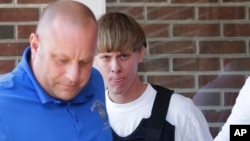 Charleston, S.C., shooting suspect Dylann Storm Roof, center, is escorted from the Shelby Police Department in Shelby, North Carolina, June 18, 2015.