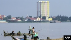 Người câu cá trên những chiếc thuyền gỗ trên sông Mekong ở Phnom Penh