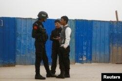 A police officer talks to men in a street in Kashgar, Xinjiang Uighur Autonomous Region, China, March 24, 2017.